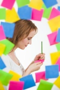 Beautiful woman writing note or idea, surrounded by lots of notes